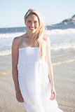 Woman in white dress smiling at camera on the beach