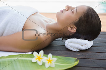 Peaceful brunette lying with eyes closed on a towel