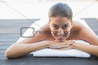 Happy brunette lying on a towel poolside