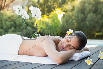 Smiling brunette lying on a towel poolside surrounded by flowers