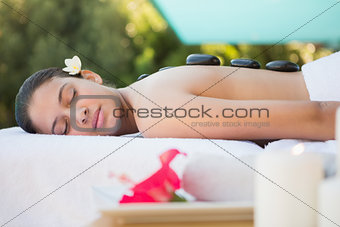 Smiling brunette lying on towel having a hot stone massage
