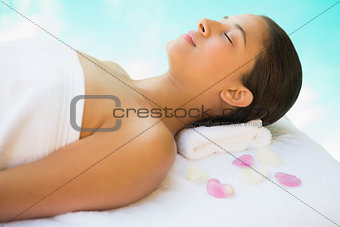 Calm brunette lying on towel with rose petals