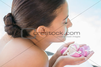 Smiling brunette lying on towel holding rose petals