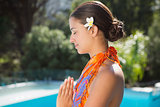 Brunette in sarong meditating by the pool