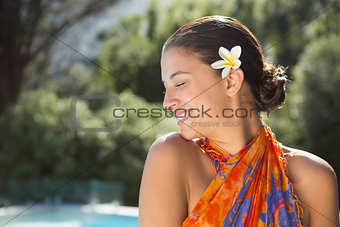 Brunette in sarong smiling by the pool