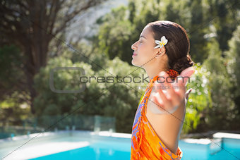 Brunette in sarong smiling by the pool with arms outstretched