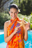 Smiling brunette in sarong showing starfish to camera