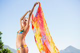 Beautiful brunette in bikini holding sarong up