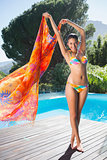 Beautiful brunette in bikini holding sarong up by the pool