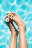 Feet dangling over swimming pool with flowers