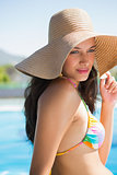 Beautiful brunette sitting by pool wearing straw sunhat