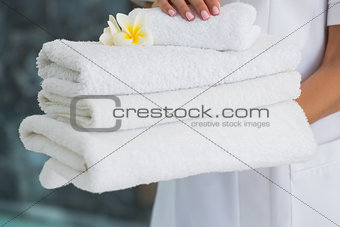 Beauty therapist holding pile of fresh white towels