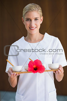 Smiling beauty therapist holding tray of treatments