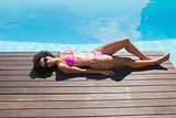 Fit woman in pink bikini lying poolside