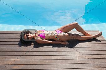 Fit woman in pink bikini lying poolside