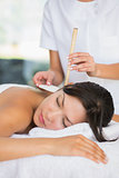 Relaxed brunette getting an ear candling treatment