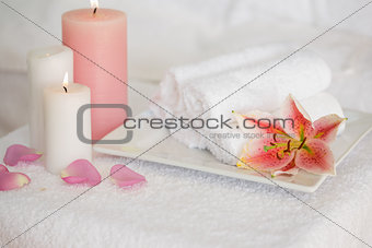 Candles and fresh white towels with lily