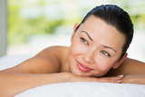 Smiling brunette lying on massage table