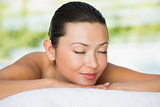 Smiling brunette lying on massage table with eyes closed