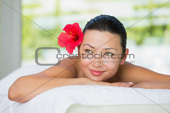Smiling brunette lying on massage table with red lily in her hair
