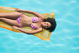 Happy woman lying on lilo in swimming pool