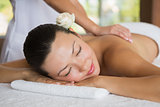 Brunette enjoying a peaceful massage with eyes closed