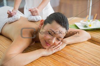Smiling brunette getting a herbal compress massage