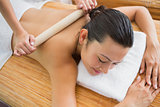 Smiling brunette getting a bamboo massage