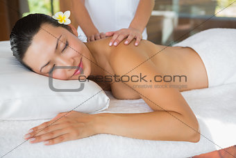 Smiling brunette getting a shoulder massage