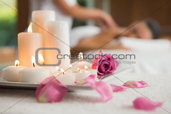 Candles and rose petals on massage table