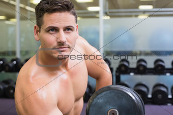 Handsome bodybuilder lifting heavy dumbbell