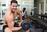 Handsome bodybuilder lifting heavy dumbbell smiling at camera