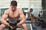 Handsome bodybuilder holding heavy black dumbbell