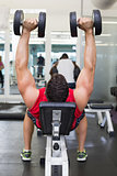 Bodybuilder lying on bench lifting dumbbells