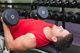 Bodybuilder lying on bench lifting heavy dumbbells