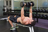 Shirtless bodybuilder lying on bench lifting heavy dumbbells