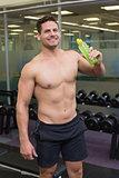 Shirtless bodybuilder drinking sports drink smiling at camera