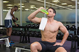 Shirtless bodybuilder drinking sports drink