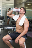 Shirtless bodybuilder drinking protein drink sitting on bench