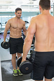 Shirtless bodybuilder lifting heavy black dumbbell looking in mirror