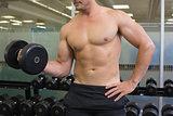 Shirtless bodybuilder lifting heavy black dumbbell