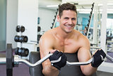 Shirtless smiling bodybuilder lifting heavy barbell weight using bench
