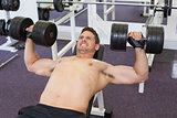 Shirtless bodybuilder lifting heavy dumbbells lying on bench