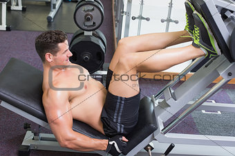 Shirtless bodybuilder working on his legs with weight machine