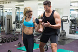Personal trainer coaching female bodybuilder lifting dumbbell