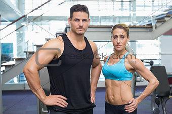 Bodybuilding man and woman frowning at camera