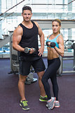Bodybuilding man and woman holding dumbbells looking at camera
