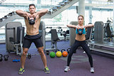 Bodybuilding man and woman lifting kettlebells