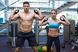 Bodybuilding man and woman lifting kettlebells looking at camera