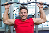Handsome smiling bodybuilder using weight machine for arms
